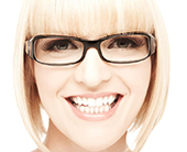 A young woman is wearing thick framed glasses and smiling at the camera. Square framed shot.